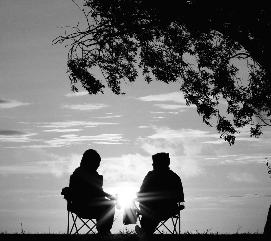 2 silhouettes de personnes discutent au pied d'un arbre sur des chaises de camping au lever du soleil, l'un semble se confier à l'autre. L'image est en noir et blanc.